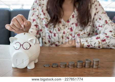 Women Are Picking Up Coins Into A Piggy Bank With Their Hands To Save Money, And It Is A Financial P