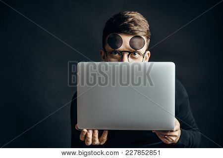 Young Smart Man Wearing Flip-up Glasses Covering Face With Laptop Looking At Camera.