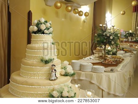 Wedding Cake With The Decoration  And Table On The Back View