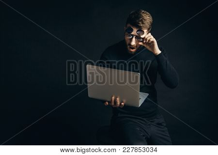 Bearded Elegant Man Wearing Stylish Flip Glasses And Looking At Laptop With Amazement.