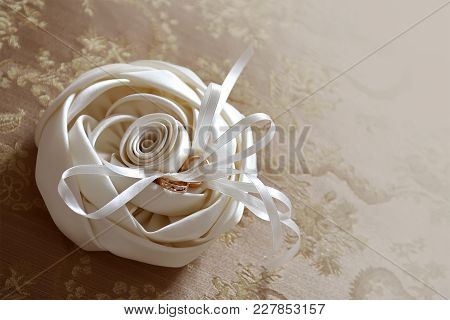 Wedding Rings On White Beautiful Cushion In The Form Of A Rose