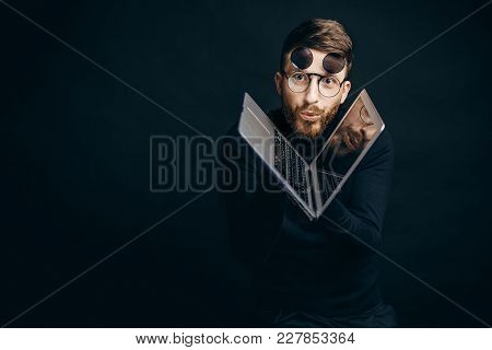Bearded Man In Flip-up Glasses Looking At Camera With Excitement Holding Laptop On Black Background.