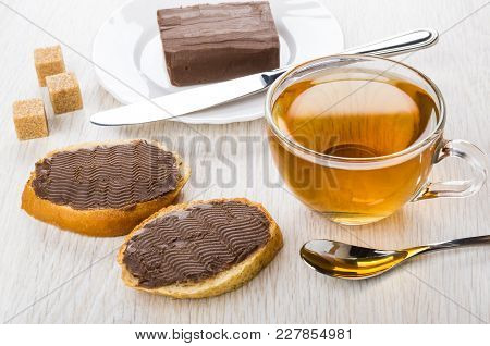 Sandwiches With Chocolate Butter, Sugar, Butter In Plate, Knife, Cup Of Tea And Spoon On Wooden Tabl