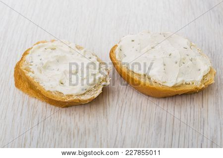 Two Sandwiches With Curd Cheese With Greens On Wooden Table
