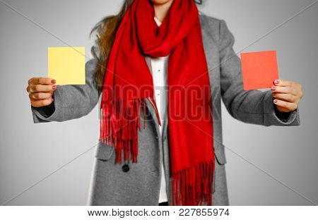 A Girl In Grey Coat And Red Scarf Holds A Yellow And Red Clean Empty Square Sticker. Isolated On Gre