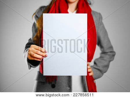 A Girl In Grey Coat And Red Scarf Keeps A Light Blue Clean Blank Sheet Of A4. Isolated On Grey Backg