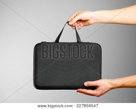 Hands Holding A Black Case. Isolated On Grey Background.