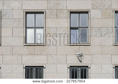 Surveillance Camera On Building Wall Under Two Windows
