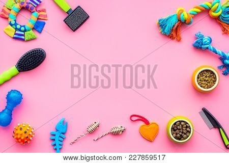 Pet Accessories. Toys Near Bowls With Animal Feed, Grooming Equipment On Pink Background Top View.