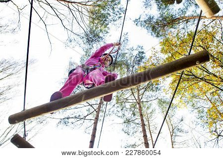 Young Girl In Harness Climbing And Trying Facilities In An Adventure Park.