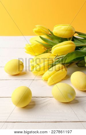 Yellow Painted Easter Eggs With Bouquet Of Tulips On Wooden Tabletop