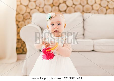 Little Baby Girl In White Lavish Dress Standing In Living Room In House On Sofa And Wooden Wall Back