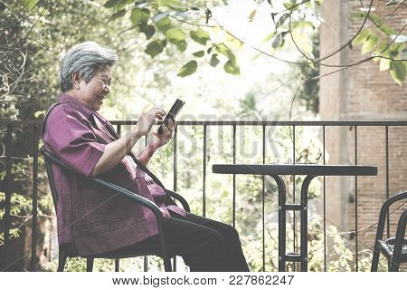 Elder Woman Holding Mobile Phone On Terrace. Elderly Female Texting Message, Using App With Smartpho
