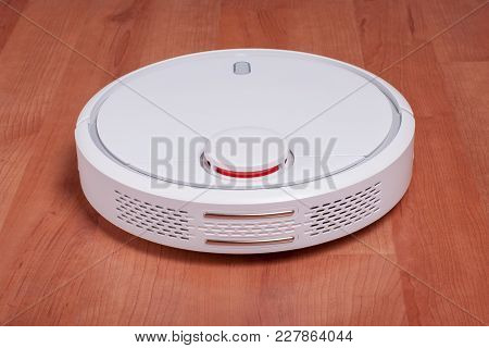 White Robot Vacuum Cleaner On Laminate Floor Cleaning Dust In Living Room. Modern Smart Electronic H