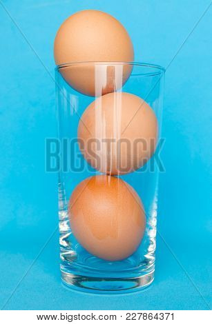Three Brown Eggs In Transparent Glass On Blue Background.
