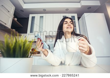 Beautiful Happy Girl Wears White Bathrobe Have Cup Of Coffee And Smartphone In The Morning Kitchen