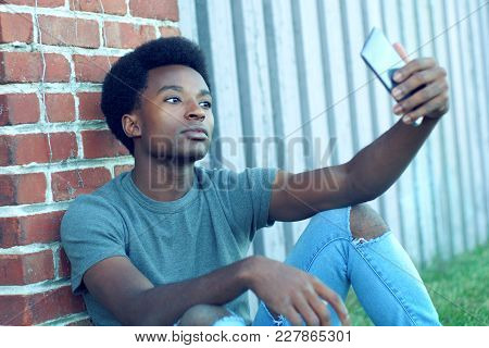 Young African Taking Selfie Sitting Outside Grass Brick Wall Cellphone Portrait Picture