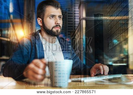 Hot Drink. Smart Attentive Experienced Employee Sitting In Front Of A Modern Computer And Holding A