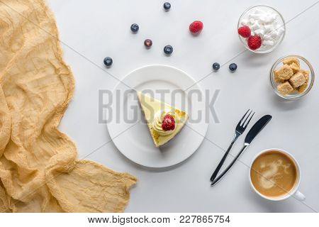 Top View Of Piece Of Cake With Berries And Coffee On White Tabletop