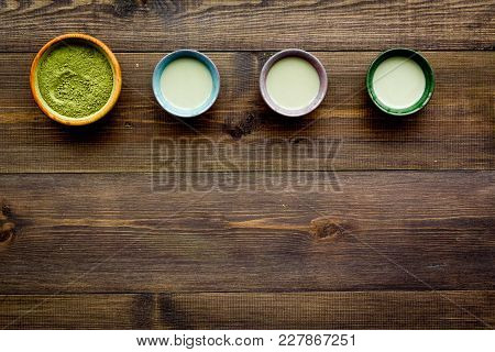 Brew Matcha Tea. Bowl With Powder And Cups With Beverage On Dark Wooden Background Top View.