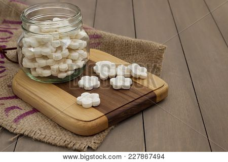 White Coconut Tapioca Cookies Spread On A Wooden Block And In A Glass Jar With A Burlap Cloth.