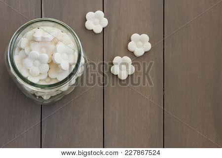 Overhead Of White Coconut Tapioca Cookies Spread In A Glass Jar.