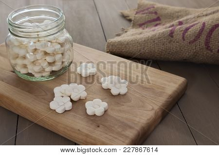 White Coconut Tapioca Cookies Spread On A Wooden Block And In A Glass Jar.