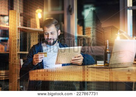 Online Shopping. Cheerful Relaxed Man Holding A Modern Tablet And Looking At The Credit Card While S
