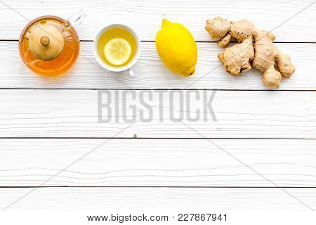 Warming Tea With Lemon And Ginger. Cup, Teapot, Ginger Root On White Wooden Background Top View.
