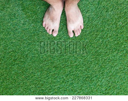 Man Standing On The Grass Field With Barefoot Close Up.