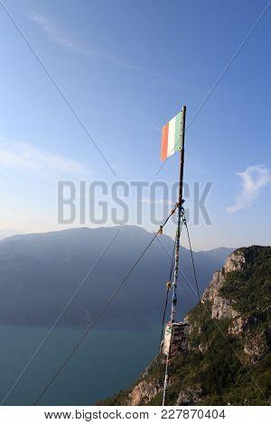 Italien Flag At Mountain Summit Cima Sat With Lake Garda Panorama, Italy
