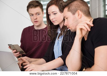 Young Businesswoman Using Laptop By Male Colleagues In Office