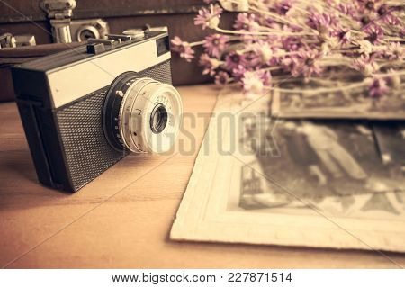 Close Up Of Old Camera Lens Over Blurred Background Of Old Leather Suitcase,  Retro Shoots And  Flow