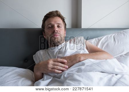 Caucasain Man In White T-shirt Lies On Bed And Looks Confident At Camera