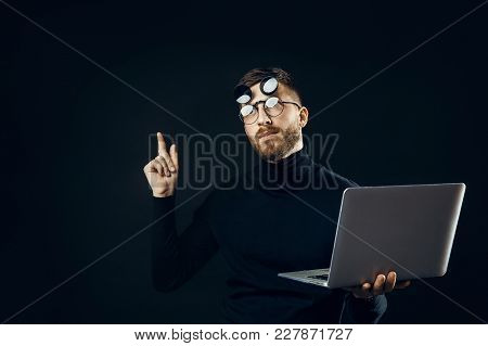Young Bearded Man In Flip-up Glasses Pointing Up Having Idea While Holding Laptop.