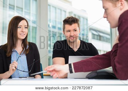 Smiling Business People Looking At Colleague Explaining At Desk In Office