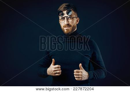 Man In Black Turtleneck And Flip-up Glasses Showing Thumbs Up At Camera On Black Backdrop.