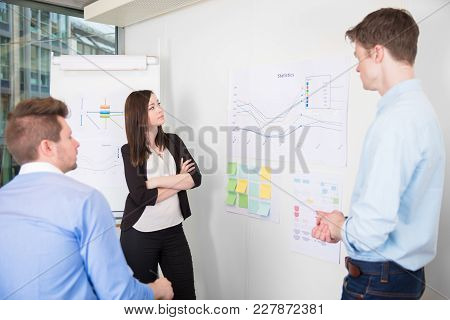 Male And Female Business People Discussing Over Line Graph In Office