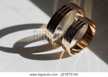 Golden Wedding Rings For Bride And Groom Standing On The Sides