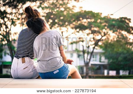 A Couple Girl Has Love And Looking Together With Sunset Time At Garden Park And River In The Evening