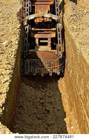 The Conveyer Bucket Of An Old Vintage Exciting And Trencher Machine Creates A Trench