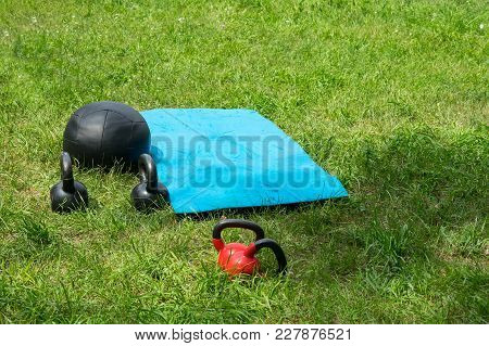Bunch Of Fitness Training Weights On Green Grass Background. Fitness Equipment: Medicine Ball, Few K