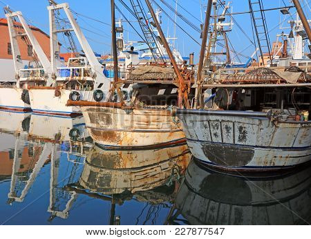 Many Big Fishing Boats Moored In The Water Canal By The Sea