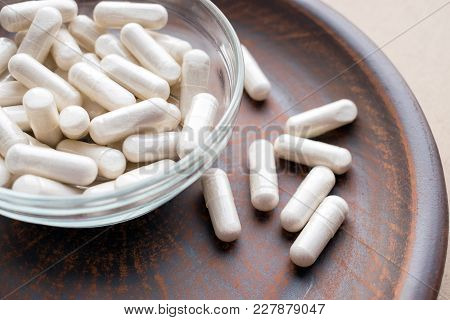 Veg Herb Capsules On Round Clay Brown Plate. Herbal Supplements Dangerous With Prescription Drugs. D