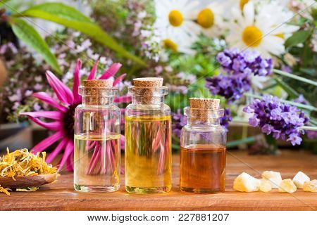 Three Bottles Of Essential Oil With Frankincense, Lavender, Echinacea, Chamomile And Other Herbs And