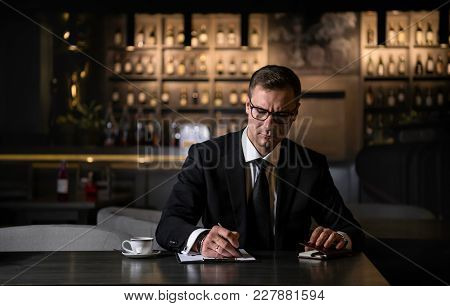 Portrait Of An Elegant, Serious And Concentrated Businessman Writing The Notes In Modern Restaurant