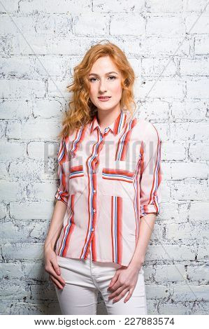 A Beautiful Young Woman Student With Red Curly Hair And Freckles Is Leaning Against A Brick Wall Of