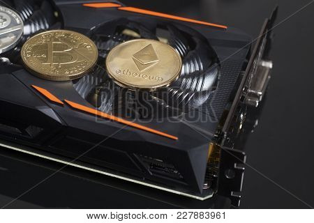 Cryptocurrency Mining Concept With Bitcoins End Ethereum On A Graphic Videocard On Black Background.