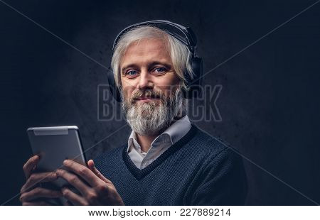 Studio Portrait Of A Handsome Senior Man Using A Tablet With Headphones Over A Dark Background.
