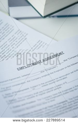 Agreement Of Employment With Pen And Laptop Lying On A Desk In A Close Up Overhead View In A Concept